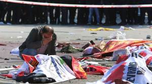 A man cries over the body of a victim, at the site of an explosion in Ankara, Turkey, Saturday, Oct. 10, 2015. The two bomb explosions targeting a peace rally in the capital Ankara has killed dozens of people and injured scores of others. The explosions occurred minutes apart near Ankara's main train station as people were gathering for the rally, organized by the country's public sector workers' trade union and other civic society groups. The rally aimed to call for an end to the renewed violence between Kurdish rebels and Turkish security forces. (AP Photo/Burhan Ozbilici)